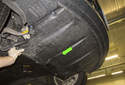 Then remove the engine splash shield in the direction of the green arrow.