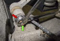 Loosen the nut (red arrow) while counter-holding the 7mm hex boss (green arrow) on the ball joint.