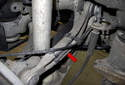Working at the rear control arm, detach the ABS wheel speed sensor harness bracket (red arrow).