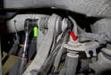 Working at the rear of the control arm, counterhold the 18mm nut (red arrow) while removing the 18mm bolt (green arrow).