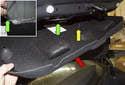 Затем потяните отделку ковра (красная стрелка) вниз и протяните кабель аварийного выпуска через отделку (желтая стрелка).