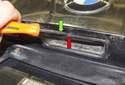 Using a small flathead screwdriver, lever the trunk release button out of the trunk lid at the top (red arrow).