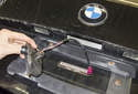Снимите спусковую кнопку с крышки багажника во время подачи жгута проводов наружу.