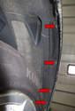 Работая в задней части колодца крыла, снимите четыре 8-миллиметровых крепежных элемента с вкладыша колодца колеса (красные стрелки).