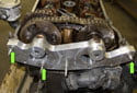 Place the VANOS set up bracket 11 6 150 onto cylinder head and evenly tighten the fasteners (green arrows) until it is flush with the cylinder head.