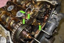Remove the four 10mm timing chain tensioner fasteners (green arrows).