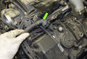 Working at the hose on the left side valve cover, squeeze the collar while pulling the hose (green arrow) off the valve cover.