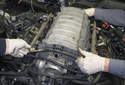 With help from a friend, lift the intake manifold up to remove it, untangling wires and hoses as you both lift it.