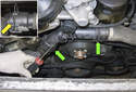 To replace the radiator hoses, use a flathead screwdriver to lever out the coolant hose retaining clips (green arrows).