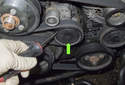Locate the accessory drive belt tensioner and remove the dust cap (green arrow) using a flathead screwdriver.