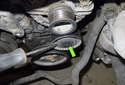 Working at the top of the alternator, remove the idler pulley dust cap (green arrow) using a flathead screwdriver.