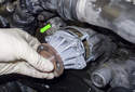 Remove the water pump from the engine by pulling it straight out in the direction of the green arrow.