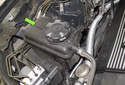 The coolant expansion tank is located on the right (passenger) side of the engine compartment (green arrow).