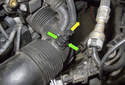 Working at the intake air duct, squeeze the release collar (green arrows) and pull the hose connection off the duct in the direction of the yellow arrow.