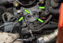 Remove the four 10mm throttle housing fasteners (green arrows).