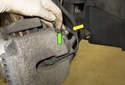 Откройте крышку выпускного устройства тормозного суппорта (зеленая стрелка) и снимите провод датчика износа колодок (желтая стрелка) с крепления.