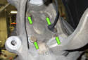Working at the back of the steering knuckle, remove the four 18mm wheel bearing fasteners (green arrows).
