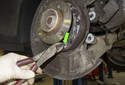 Next, unhook the lower return spring from the parking brake shoes (green arrow).