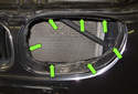 When installing the grille, align the tabs with holes in the bumper cover (green arrows).
