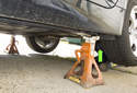 Jacking rear of vehicle: When using a hydraulic floor jack to lift the rear of the vehicle, place the hydraulic floor jack under a control arm (green arrow), raising one side at a time.