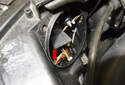 High beam bulb: Rotate the high beam bulb holder (red arrow) 45 degrees and remove it from the headlight.