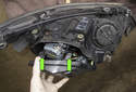 Headlight assembly: Remove the low beam access door by pressing the release tabs (green arrows) and removing.