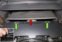Working at the top of the steering column trim panel, lever the flexible trim (red arrow) off the steering column upward, using a plastic prying tool.
