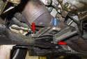 Working below the catalytic converters, remove the two 10mm heat shield (blue arrow) fasteners (red arrows).