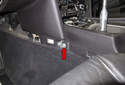 Then, remove the 10mm fasteners located under the carpet trim panels (red arrow).