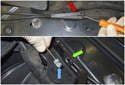 Working at the left side of the front fender near the strut tower, open the hood release cable junction box (red arrow).