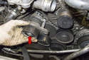 Tensioner: Loosen the T45 Torx fastener (red arrow) and remove the tensioner with the lower idler pulley.