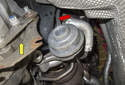 Working under the vehicle ahead of the right side transmission bell housing (yellow arrow), remove the vacuum hose (red arrow) from the rear turbocharger waste gate.