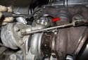 Working at the top of the turbocharger, remove the T30 Torx oil line fastener (red arrow).