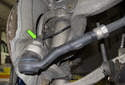 Working at the outer tie rod, remove the 21mm tie rod end nut (green arrow).