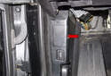 Working at the driver side kick panel, remove the OBD II connector access door (red arrow).
