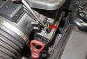 Using a flathead screwdriver, unclip the two clips located at the intake air housing connection.