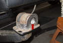Pull trailing arm down away from body and place a block of wood between trailing arm and body.