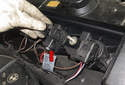Unlock the ignition coil electrical connector (red arrow) by pulling the tab up 90 degrees.