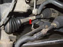 The front drive axle (red arrow) on BMW X3 models connects the front differential to the front drive wheel.