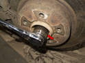 Remove the axle nut using a 36mm 12 point socket and a ratchet (red arrow).