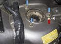 Working at the strut tower, remove the three 13mm strut mounting nuts (blue arrows).