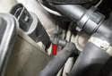 To replace the headlight pump, first remove the washer hose by pressing the release tab on the hose, then pull it straight off.