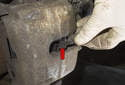 The brake pad wear sensor on the front axle is located in the left front brake caliper (red arrow).