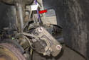 Remove brake caliper bracket from wheel carrier and hang the caliper using a piece of metal coat hanger (red arrow) or rope.