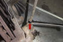 Working at brake caliper using a 14mm line wrench, loosen brake hose (red arrow).