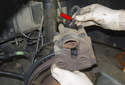 Remove brake caliper from mounting bracket and unscrew brake hose (red arrow) from caliper.