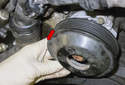 Next, remove the water pump pulley from the water pump (red arrow).