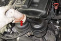Use a suction pump (red arrow) to remove the fluid from the reservoir.