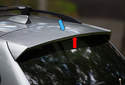 The third brake light (red arrow) on X3 models is mounted in the spoiler (blue arrow).