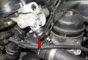 Using a 19mm wrench, remove the VANOS oil line banjo bolt (red arrow), (below oil filter housing).